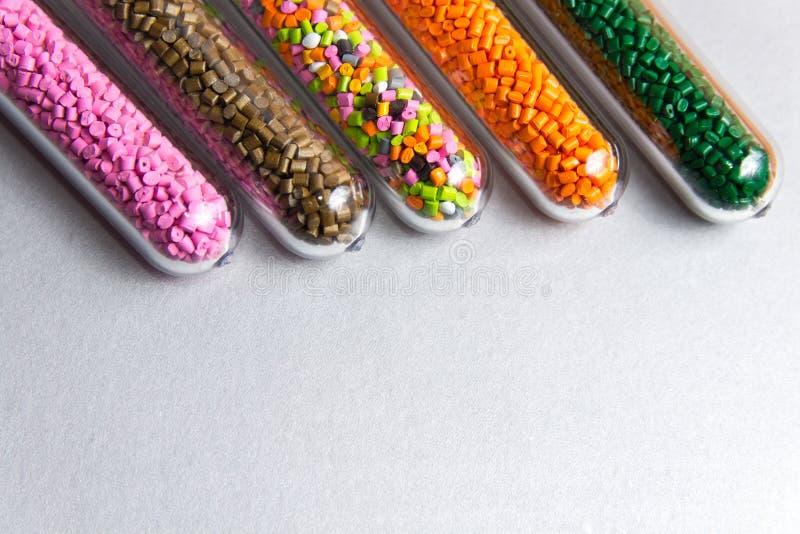 pelotas plásticas Tintura polimérico em uns tubos de ensaio no fundo cinzento imagens de stock royalty free