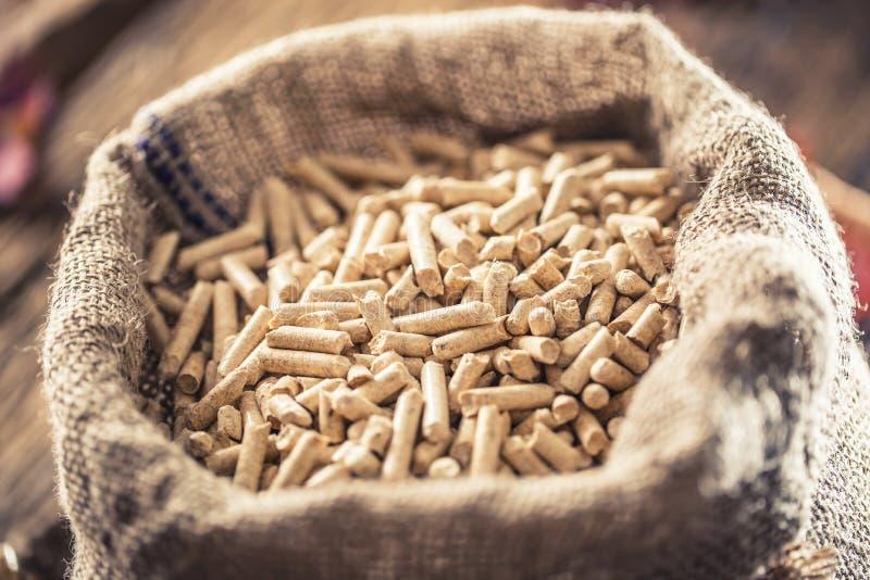 Pelotillas presionadas de madera de la biomasa en saco viejo foto de archivo
