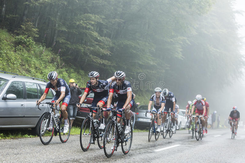 The Peloton in a Misty Day - Tour de France 2014. Col de Platzerwasel,France - July 14, 2014: The peloton on the climbing road to mountain pass Platzerwasel in royalty free stock photos