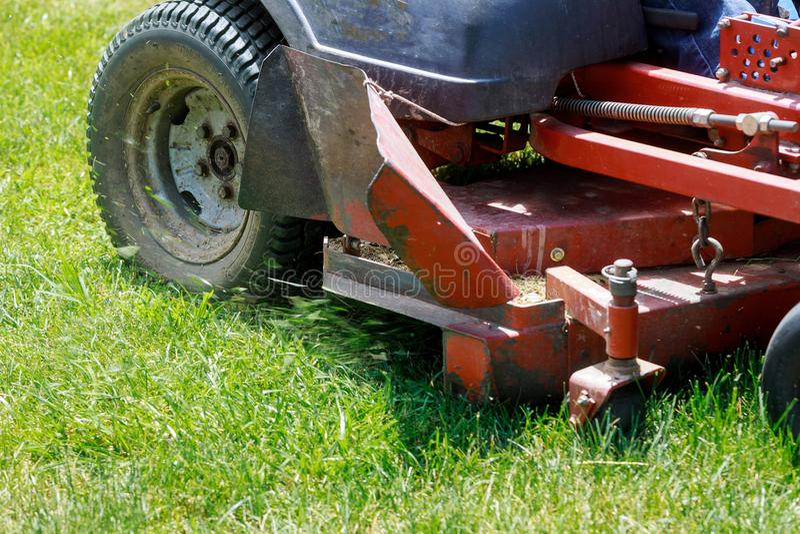 Pelouses de fauchage, tondeuse à gazon sur l'herbe verte, équipement d'herbe de faucheuse, outil de fauchage de travail de soin d images libres de droits