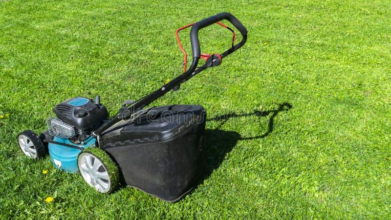 Pelouses de fauchage Tondeuse à gazon sur l'herbe verte Équipement d'herbe de faucheuse Outil de fauchage de travail de soin de j photos libres de droits