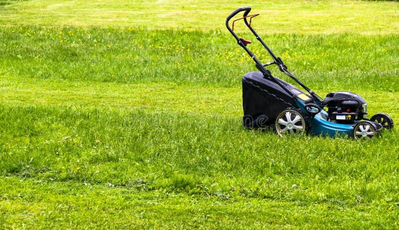 Pelouses de fauchage Tondeuse à gazon sur l'herbe verte Équipement d'herbe de faucheuse Outil de fauchage de travail de soin de j photos stock