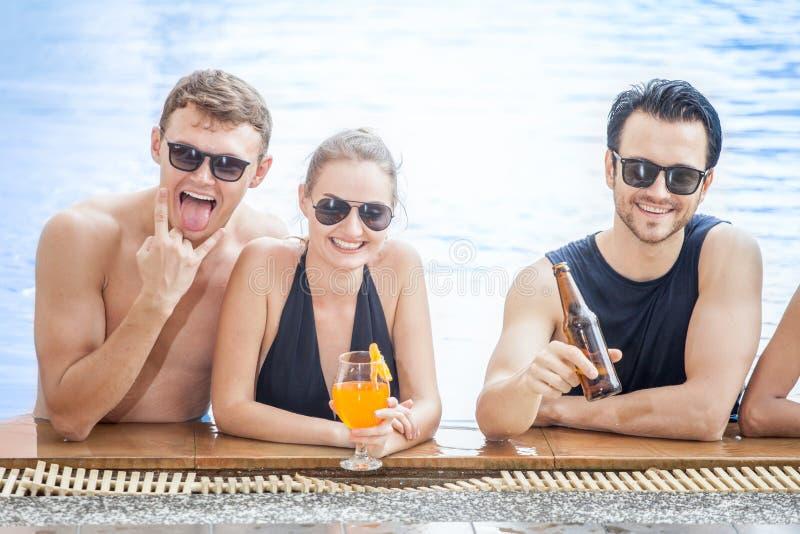 Pelple tres en el grupo de amigos que hacen el partido en la piscina y el Dr. fotografía de archivo libre de regalías