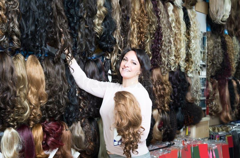 Peluca elegante femenina morena en tienda imagenes de archivo
