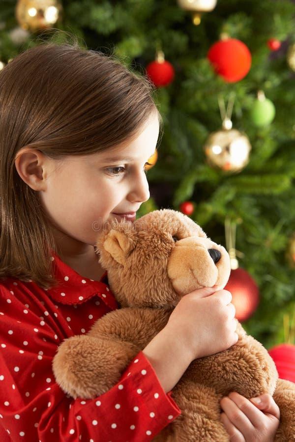Peluche de abrazo de la muchacha delante del árbol de navidad fotografía de archivo libre de regalías
