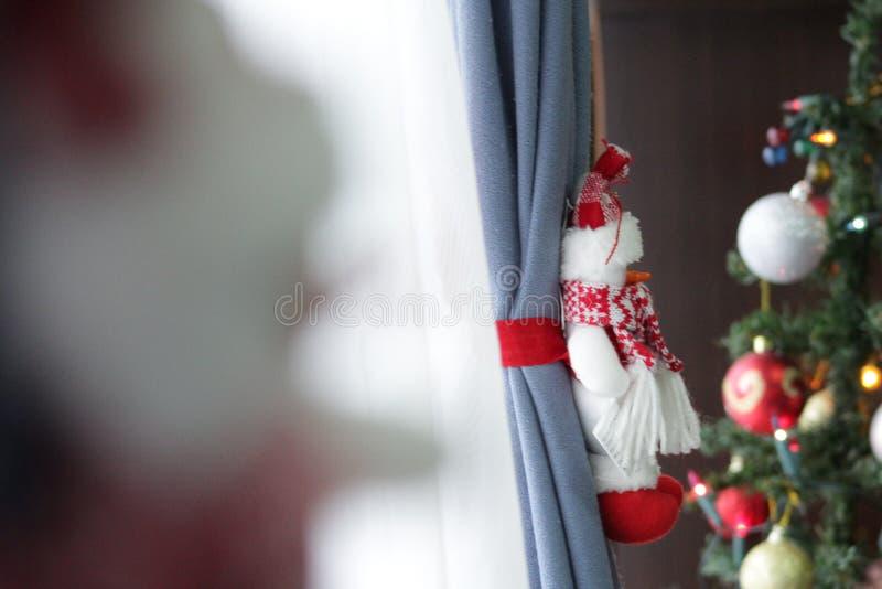 Peluche del muñeco de nieve al lado de un árbol de los chritsmas imagen de archivo