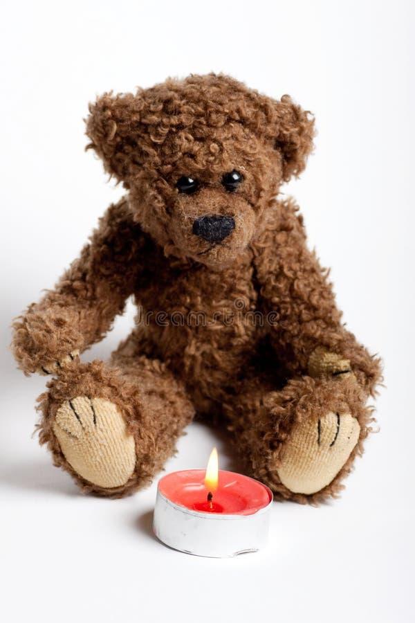 Peluche do urso do brinquedo e vela ardente. imagem de stock