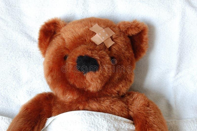 Peluche doente com ferimento na cama fotos de stock royalty free