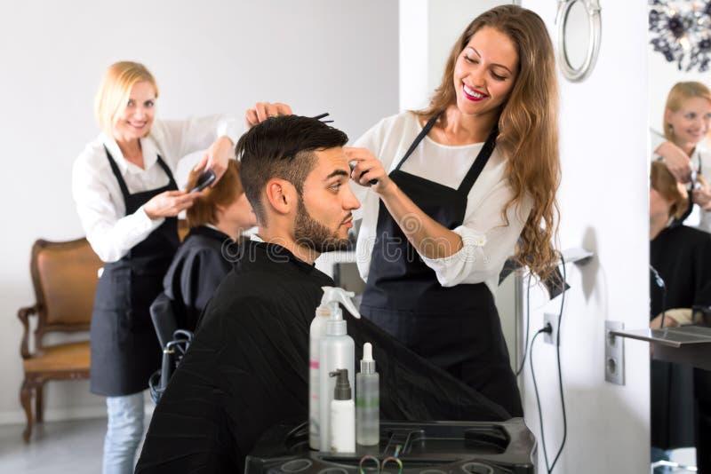 Peluquero atractivo que hace corte de pelo en hombre foto de archivo