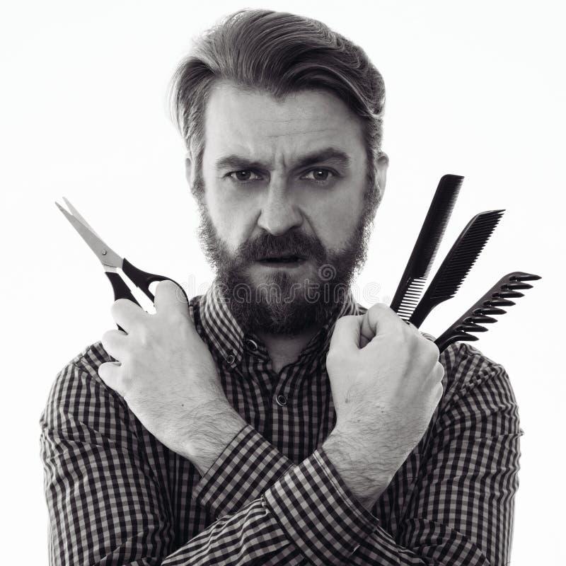 Peluquero barbudo serio que sostiene tijeras y un peine fotos de archivo libres de regalías