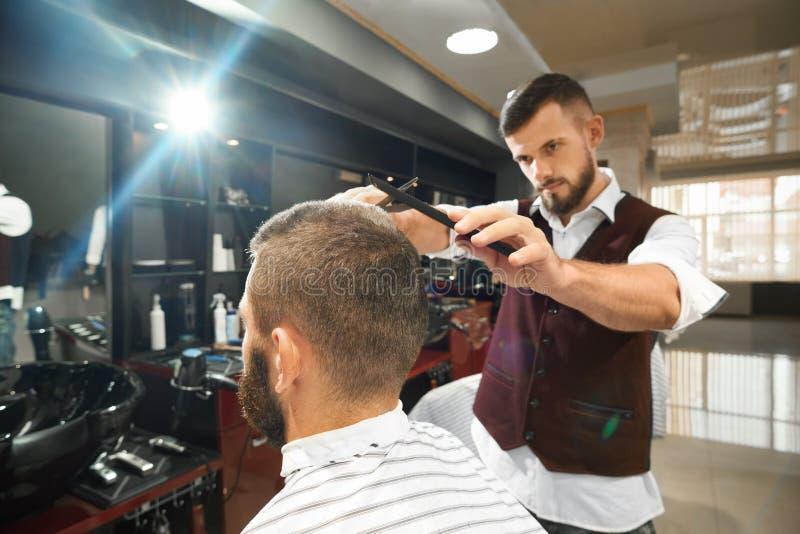 Peluquero brutal que hace corte de pelo elegante en barbería fotos de archivo