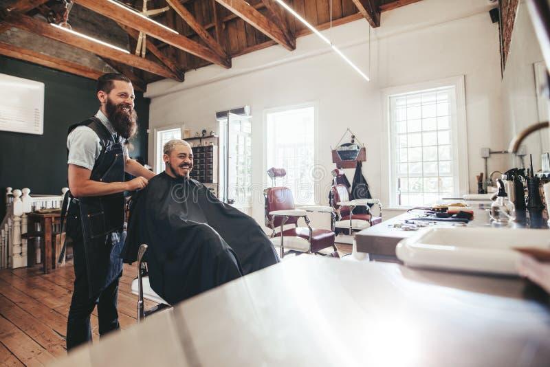 Peluquero con el cliente que se sienta en el salón y la sonrisa imagen de archivo