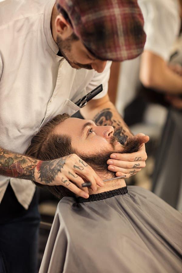 Peluquero con la maquinilla de afeitar foto de archivo