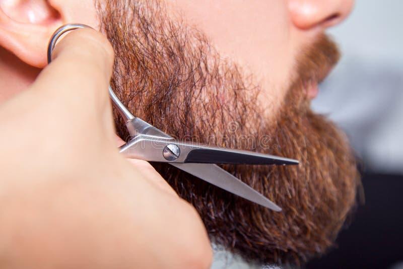 Peluquero con las tijeras que afeitan al hombre barbudo fotos de archivo libres de regalías