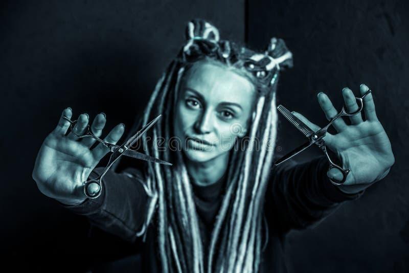 Peluquero de la muchacha con los dreadlocks que sostienen el primer de las tijeras a disposici?n fotografía de archivo libre de regalías