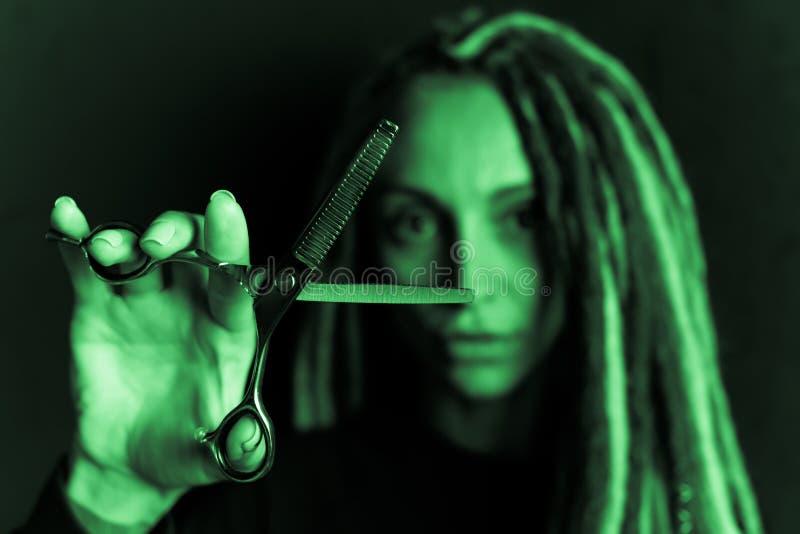 Peluquero de la muchacha con los dreadlocks que sostienen el primer de las tijeras a disposici?n fotos de archivo libres de regalías