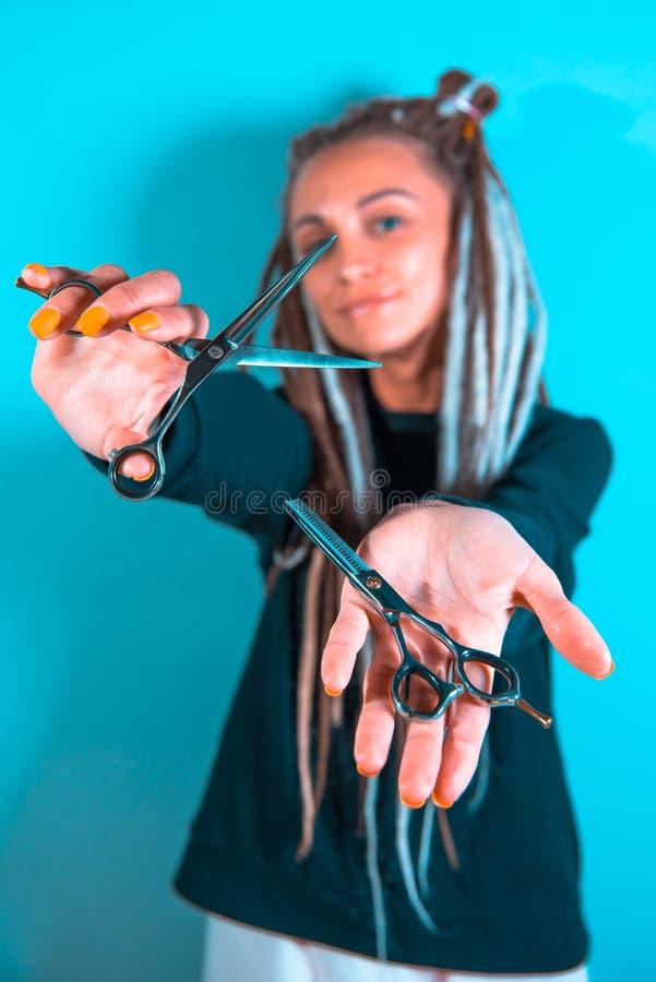 Peluquero de la muchacha con los dreadlocks que sostienen el primer de las tijeras a disposici?n imagen de archivo libre de regalías