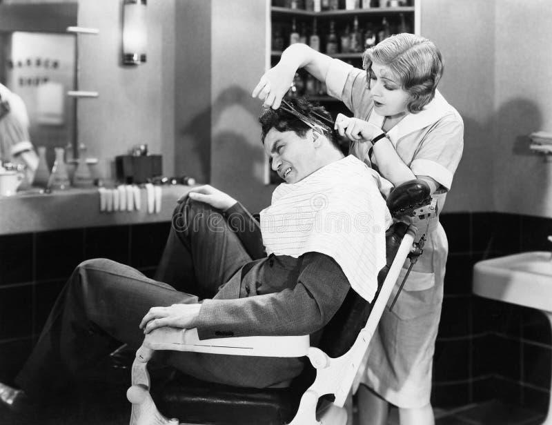Peluquero de la mujer que corta el pelo de un hombre (todas las personas representadas no son vivas más largo y ningún estado exi foto de archivo libre de regalías