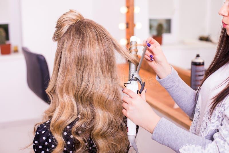 Peluquero de la mujer que hace el peinado usando el hierro que se encrespa para el pelo largo de la hembra joven imagen de archivo libre de regalías