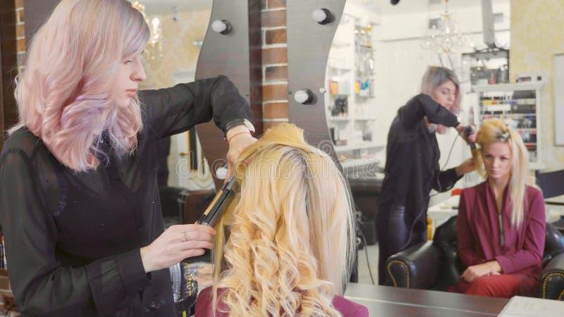Peluquero de la mujer que hace rizos en el pelo rubio con hierros que se encrespan en el salón de belleza fotos de archivo
