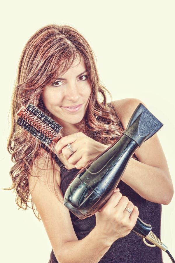 Peluquero de sexo femenino que sostiene el hairdryer y el cepillo fotografía de archivo