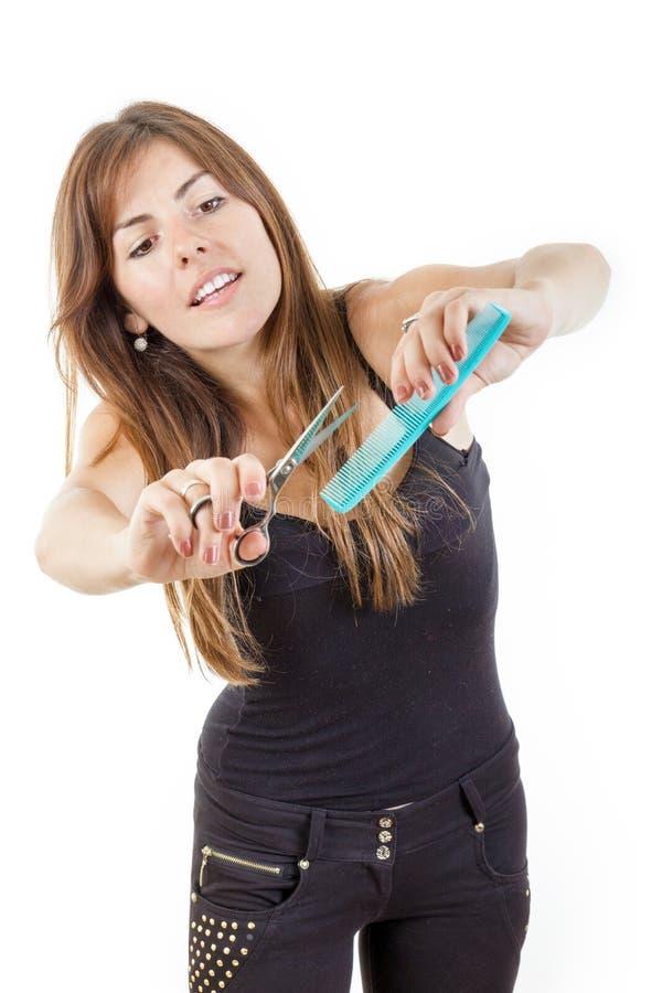 Peluquero de sexo femenino sonriente que usa el peine y las tijeras aislados imagen de archivo