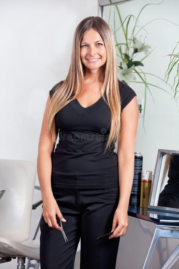 Peluquero de sexo femenino Standing At Salon fotos de archivo libres de regalías