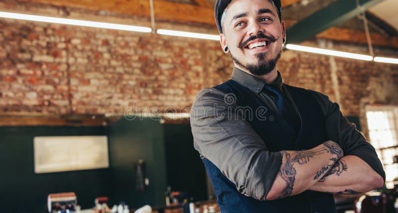 Peluquero de sexo masculino joven feliz que parece ausente y sonrisa fotos de archivo libres de regalías