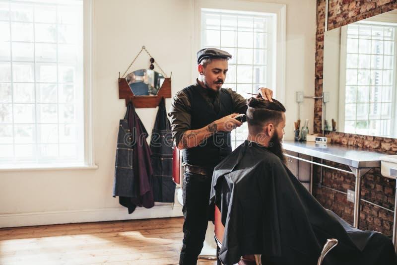 Peluquero de sexo masculino que da corte de pelo del cliente fotos de archivo