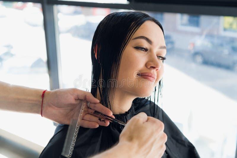 Peluquero de sexo masculino que hace un corte de pelo para una muchacha morena hermosa en salón profesional de la peluquería fotografía de archivo