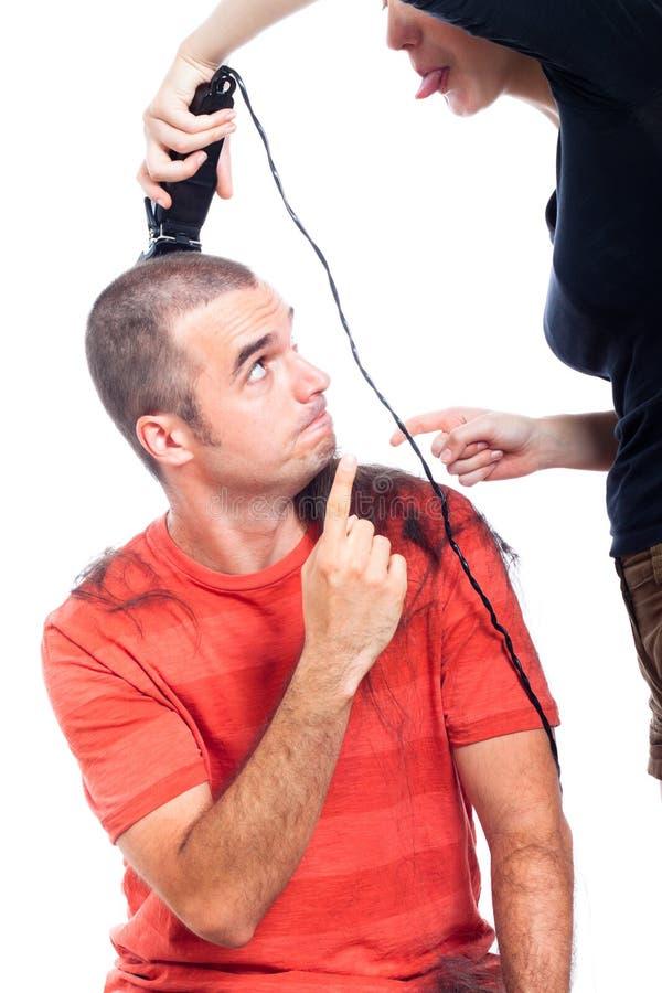 Peluquero divertido que afeita el pelo del hombre imagen de archivo