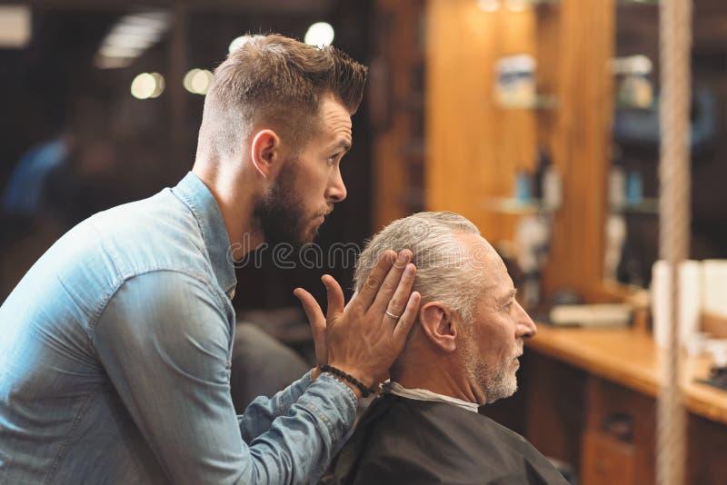 Peluquero elegante que forma el corte de pelo del cliente en la barbería fotos de archivo