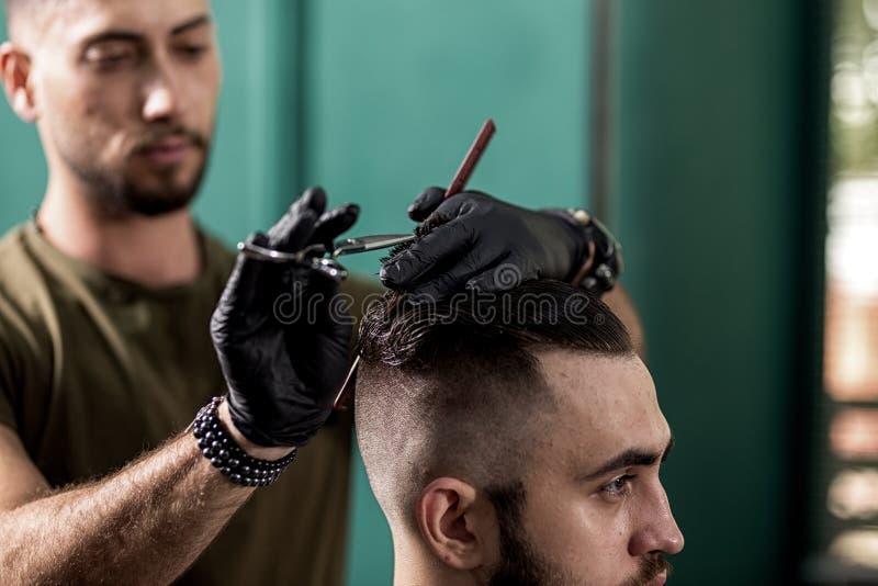 Peluquero en cortes negros de los guantes con el pelo de las tijeras del hombre elegante en una barbería fotos de archivo libres de regalías