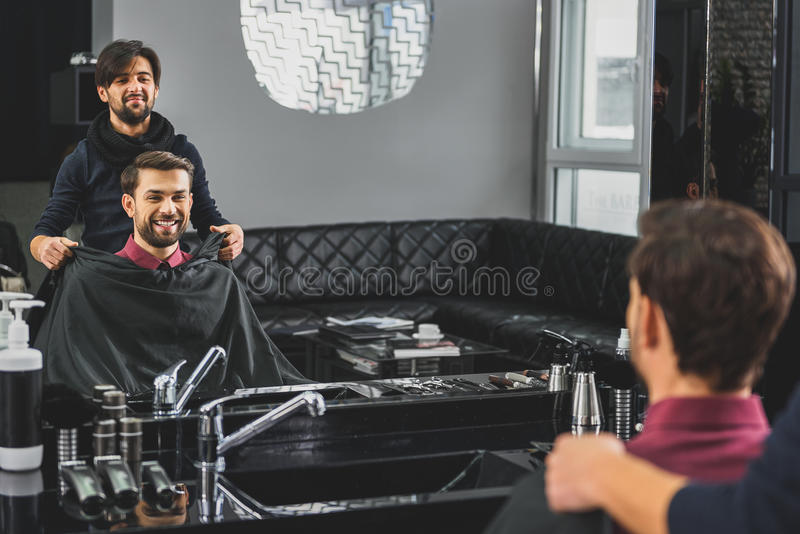 Peluquero experto que prepara al cliente para el corte de pelo foto de archivo