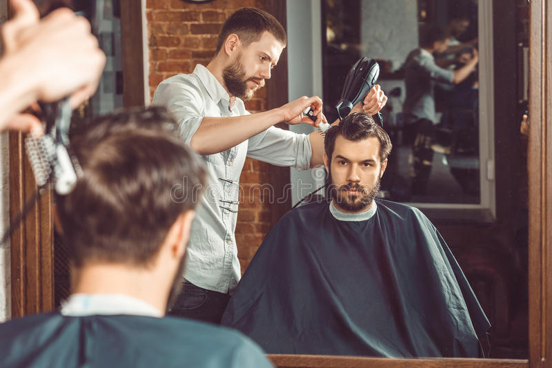 Peluquero hermoso joven que hace corte de pelo de hombre atractivo en barbería imagenes de archivo