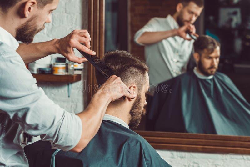 Peluquero hermoso joven que hace corte de pelo de hombre atractivo en barbería fotografía de archivo libre de regalías
