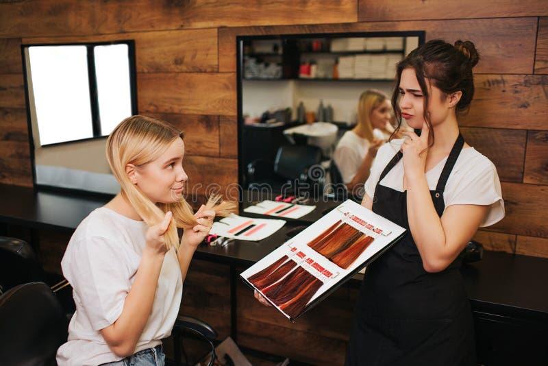 Peluquero profesional con el delantal negro que piensa en coloración del cabello del cliente femenino mientras que sostiene la pa fotografía de archivo