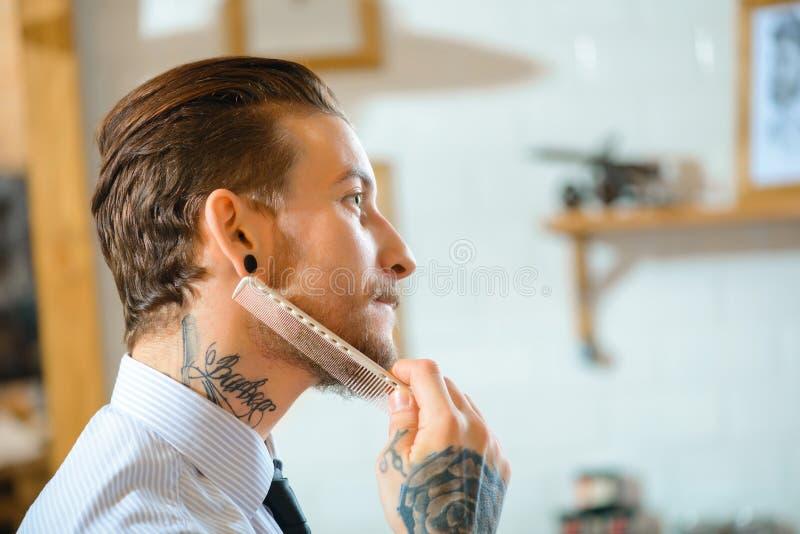 Peluquero profesional que cepilla su barba foto de archivo libre de regalías
