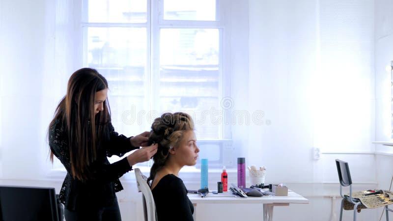 Peluquero profesional que hace el peinado para la mujer bonita joven imagenes de archivo