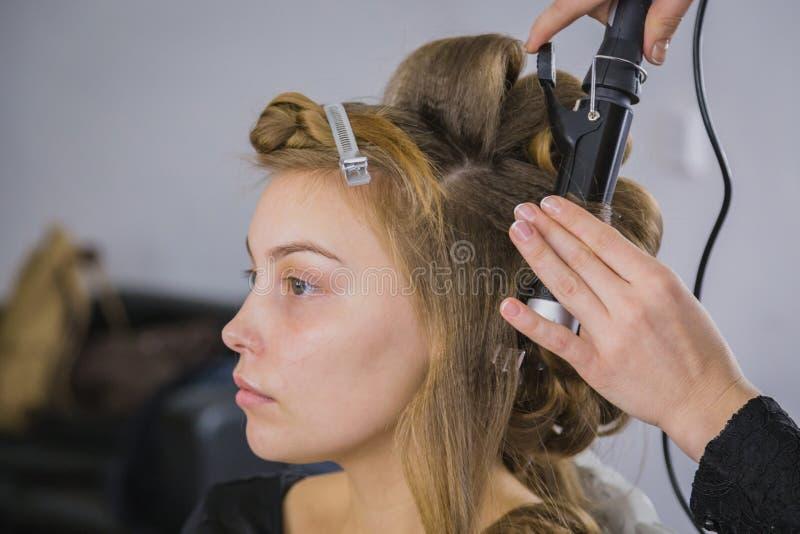 Peluquero profesional que hace el peinado para la mujer bonita joven - la fabricación se encrespa fotos de archivo