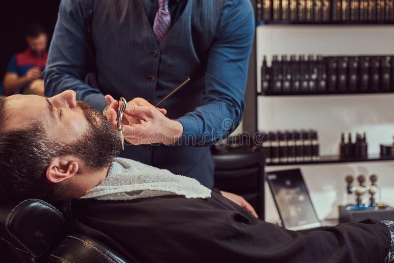 Peluquero profesional que modela la barba con las tijeras y el peine en la barbería fotografía de archivo