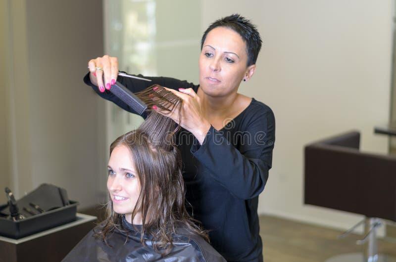 Peluquero que arregla el pelo de una mujer joven imagen de archivo
