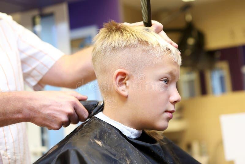Peluquero que arregla el pelo rubio del muchacho joven fotos de archivo