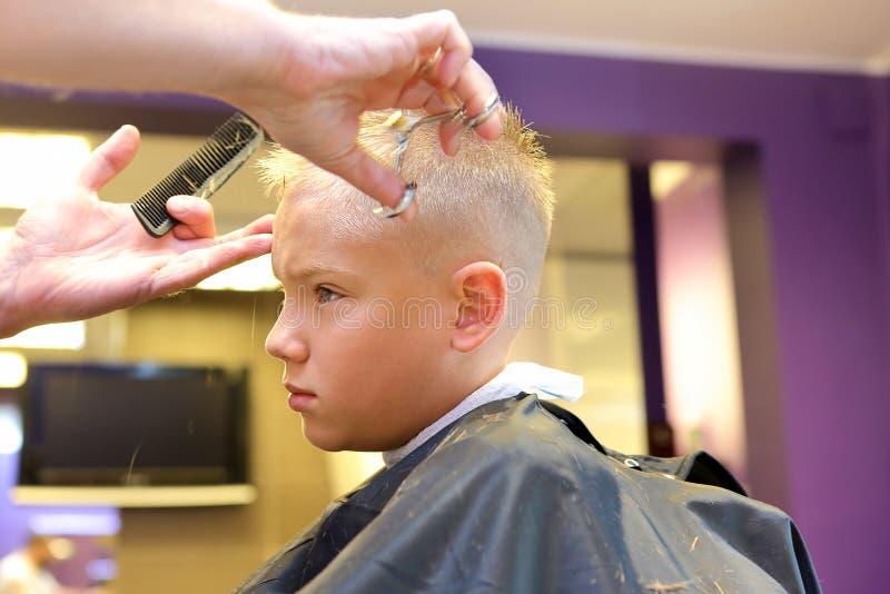 Peluquero que arregla el pelo rubio del muchacho joven fotos de archivo libres de regalías