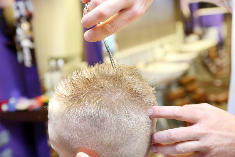 Peluquero que arregla el pelo rubio del muchacho joven foto de archivo