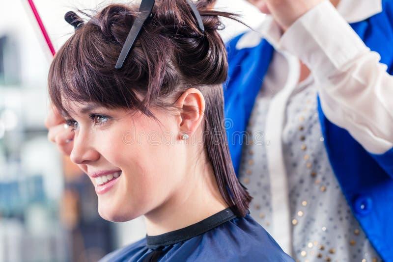 Peluquero que diseña el pelo de la mujer en tienda fotos de archivo