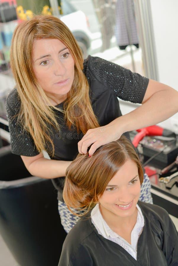 Peluquero que diseña el pelo del ` s de la señora imágenes de archivo libres de regalías