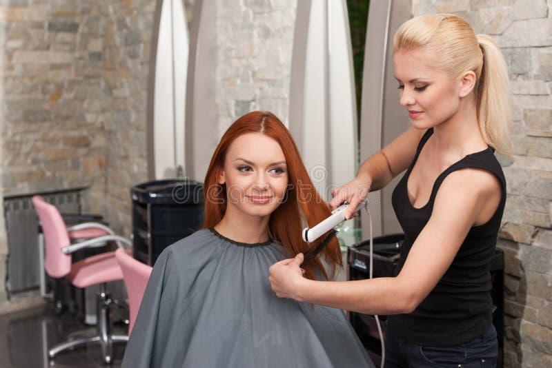 Peluquero que endereza el pelo rojo con hierros del pelo imagenes de archivo