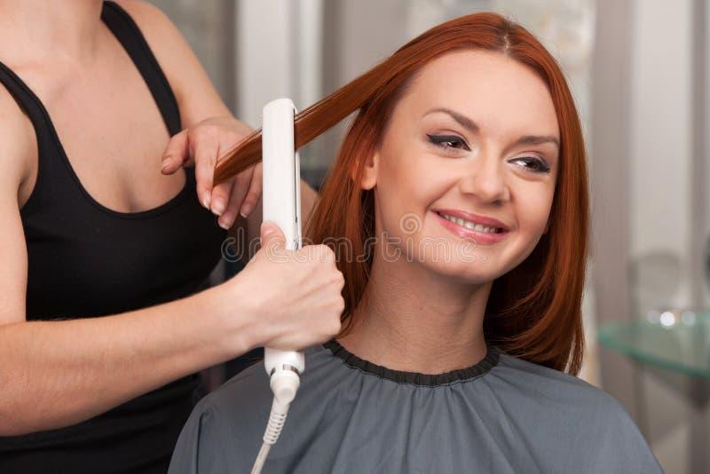 Peluquero que endereza el pelo rojo largo con hierros del pelo foto de archivo