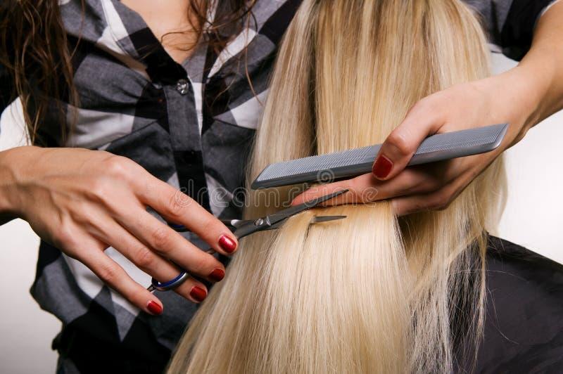 Peluquero que hace corte de pelo imagenes de archivo